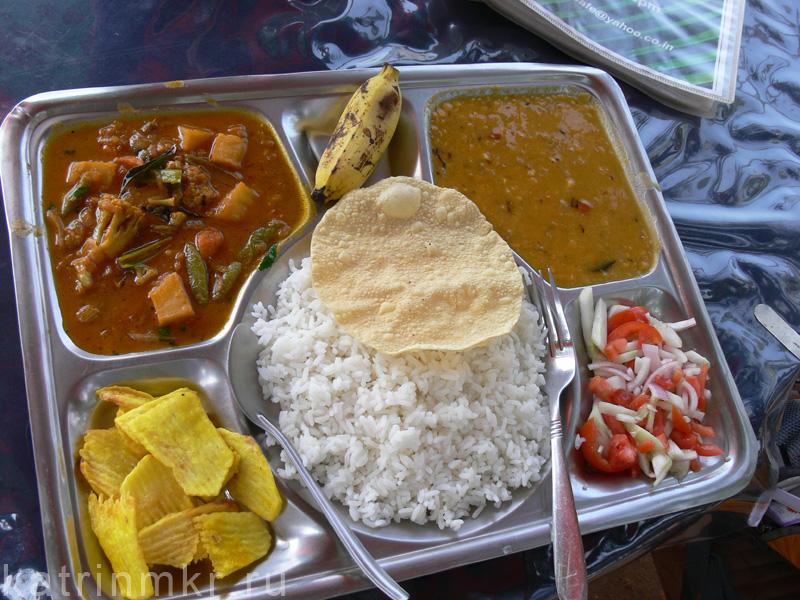 Вегетарианское Thali - рис, чечевичная похлебка (дал), помидоры с луком, овощи в кари и чипсы.